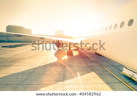 Airplane at terminal gate ready for takeoff - Modern international airport at sunset - Travel concept around the world - Wide angle distortion with rose quartz filter and enhanced sunshine lens flare - stock photo