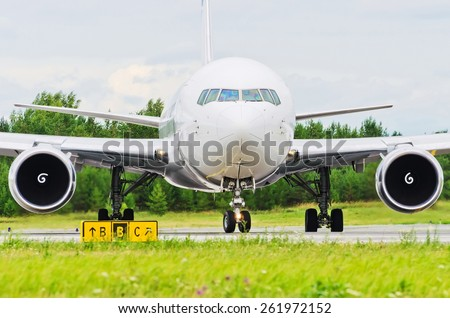 Airplane blue sky clouds flight airport grass green taxi - stock photo