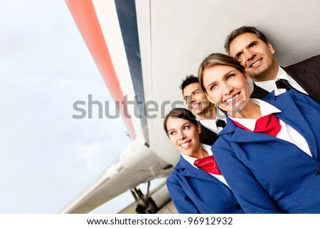 Airplane cabin crew at the airport smiling - stock photo