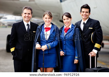 Airplane cabin crew standing at the airport with bags - stock photo