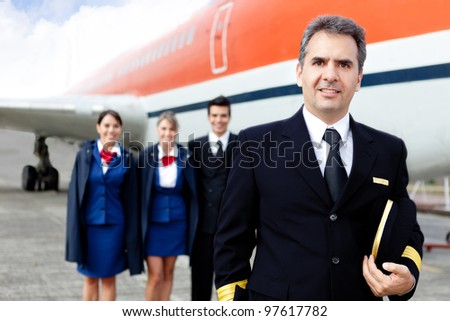 Airplane captain with crew at the airport smiling - stock photo
