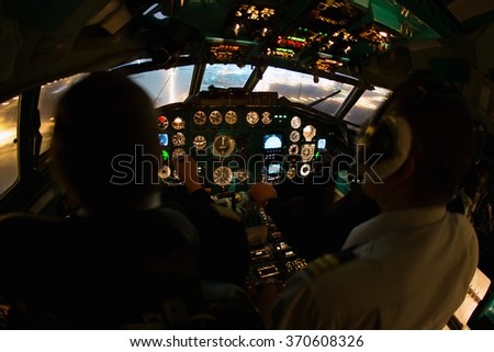 Airplane cockpit crew performs the night landing in airport  - stock photo