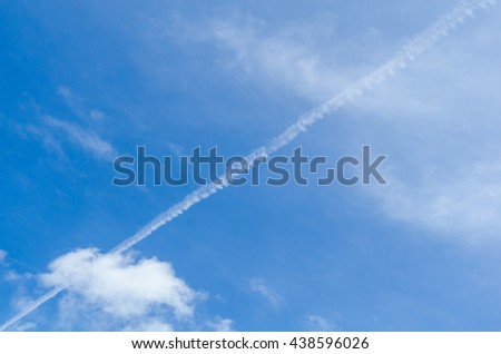 Airplane contrail against beautiful blue sky with delicate clouds