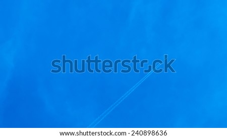 airplane contrail on blue sky and text space - stock photo