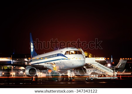 Airplane docked at the terminal and ready for takeoff. Modern international airport at night. - stock photo