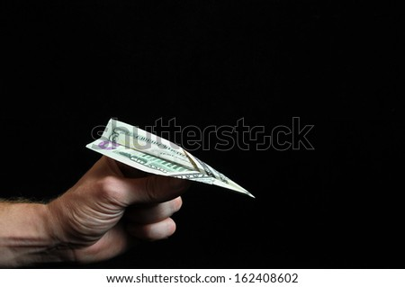 Airplane Dollar And an Hand on a Black Background - stock photo