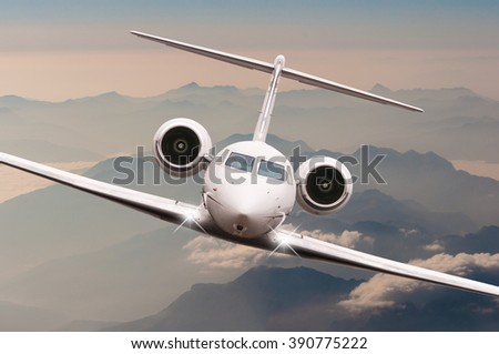 Airplane fly over clouds and Alps mountain on sunset. Front view of a big passenger or cargo aircraft, business jet, airline. Transportation, Business travel concept - stock photo