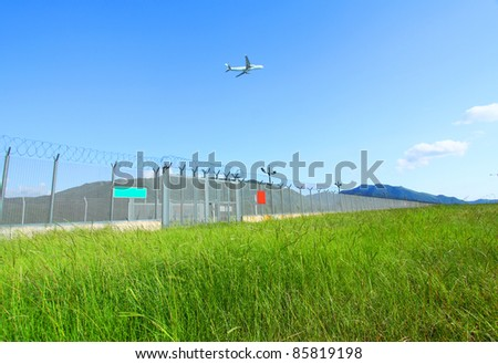 Airplane fly over the green grasses - stock photo