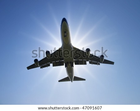Airplane fly under sunlight - stock photo