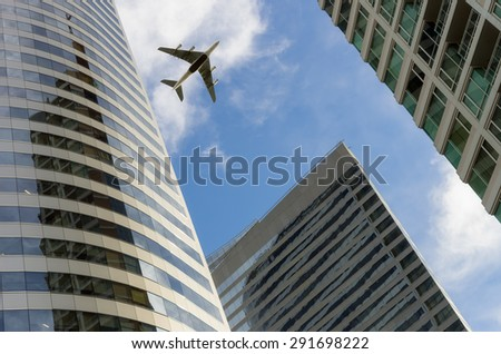 Airplane flying above glass office buildings. Wide lens effect. - stock photo