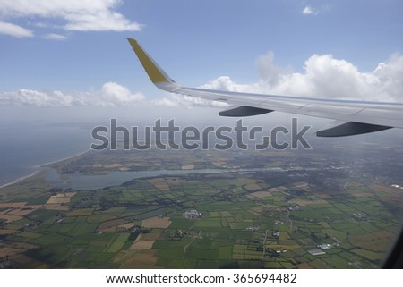 Airplane flying above some green fields - stock photo