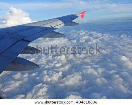 Airplane flying above the clouds, Aircraft wing over clouds - airtransport to travel. window view from airplane