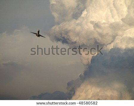 airplane flying close to the storm - stock photo