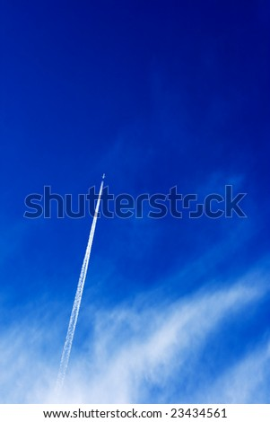 airplane flying from the clouds on a blue sky - stock photo