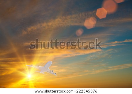 Airplane flying high in sky in beams of sunset - stock photo