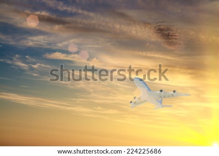 Airplane flying high in sky in beams of sunset