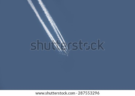 airplane flying high in the sky emitting condensation trail - stock photo