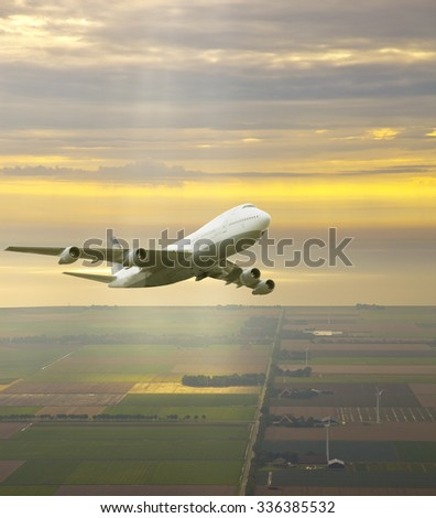 Airplane flying in beautiful yellow sky - stock photo