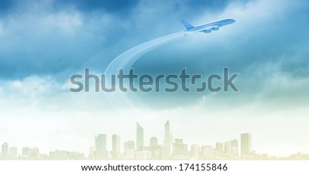 Airplane flying in blue sky above modern city - stock photo