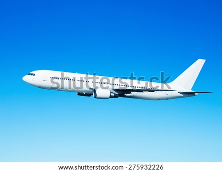 Airplane flying in the blue sky. isolated on blue.  - stock photo