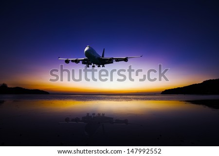 Airplane flying on tropical colorful evening sky over the sea at beautiful sunset with reflection - stock photo