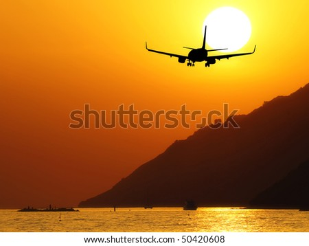 airplane flying ont the sea at sunset