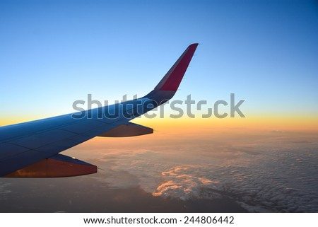 airplane flying over clouds with evening sky - view from window of airplane - stock photo