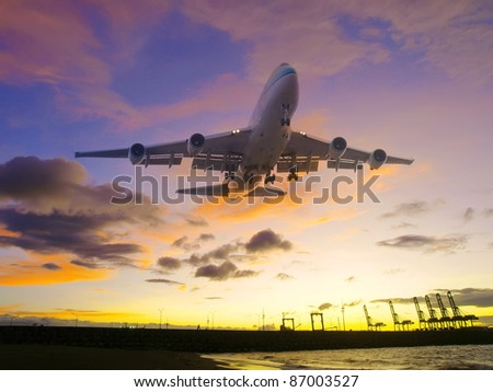 Airplane flying over seacoast - stock photo