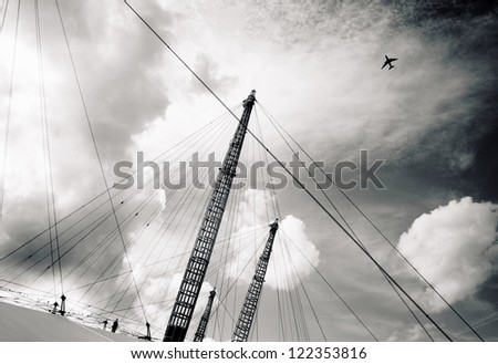 Airplane flying through clouds over Millennium o2 Dome Greenwich Peninsula, London England UK - stock photo