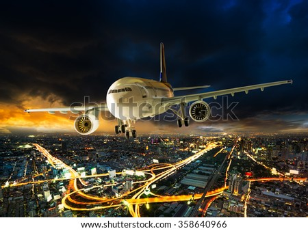 Airplane for transportation flying over the night scene city on beautiful sunset background - stock photo