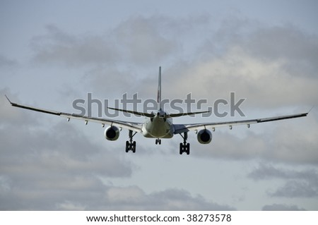 Airplane from the back end. It is ready to land with all wheels down. - stock photo