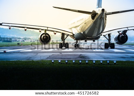 Airplane goes to the position for takeoff at an airport runway at mysteriously retro dark and bright twilight (copy space)/Ready for Take Off - stock photo