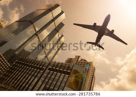 Airplane in a golden sky with modern buildings