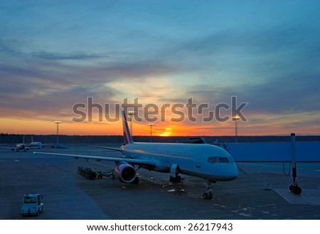 Airplane in airport at sunset - stock photo