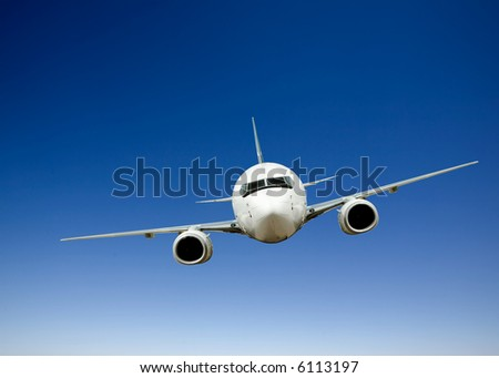 Airplane in flight against a bright blue sky - stock photo