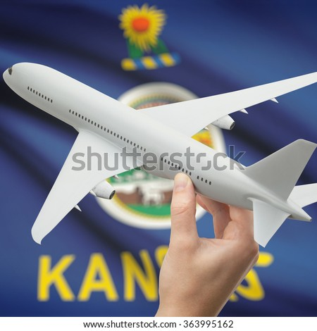 Airplane in hand with local US state flag on background series - Kansas - stock photo