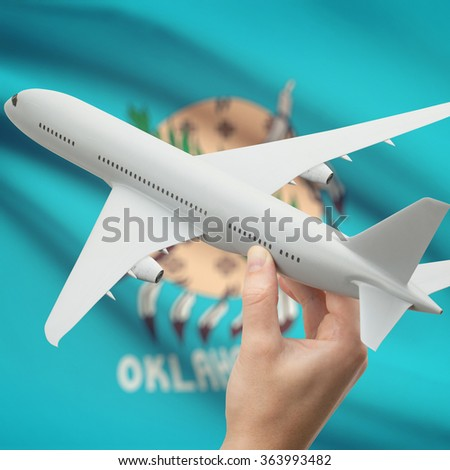 Airplane in hand with local US state flag on background series - Oklahoma - stock photo