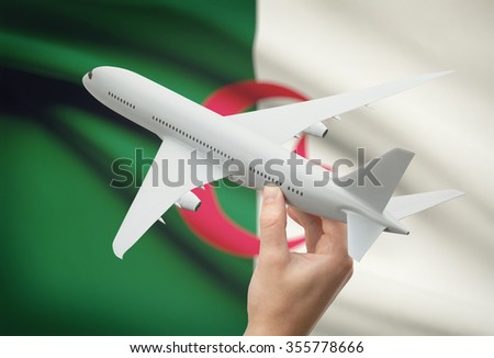 Airplane in hand with national flag on background - Algeria - stock photo