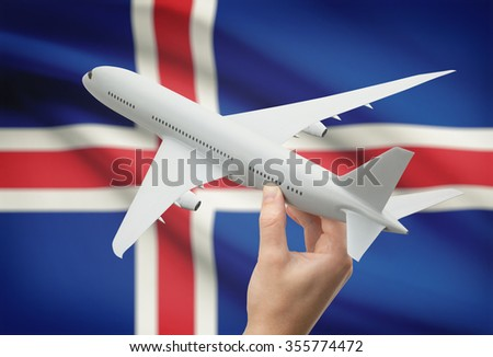 Airplane in hand with national flag on background - Iceland - stock photo