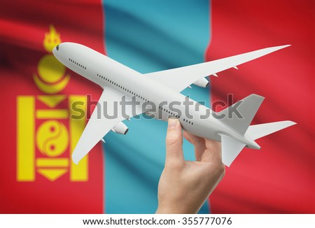 Airplane in hand with national flag on background - Mongolia - stock photo