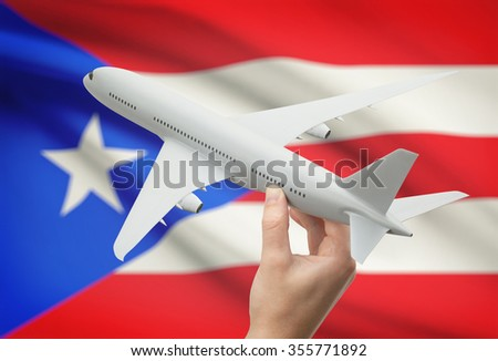 Airplane in hand with national flag on background - Puerto Rico - stock photo