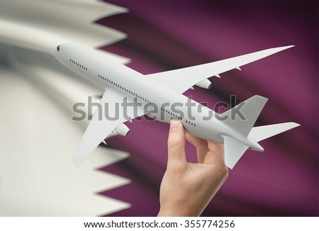 Airplane in hand with national flag on background - Qatar - stock photo