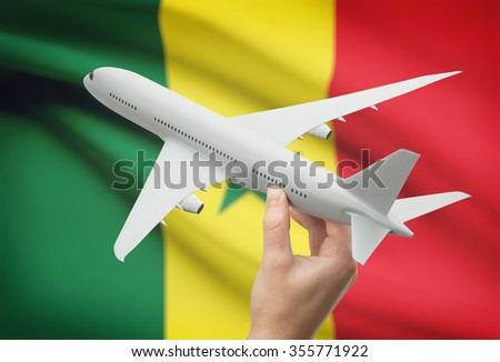 Airplane in hand with national flag on background - Senegal - stock photo