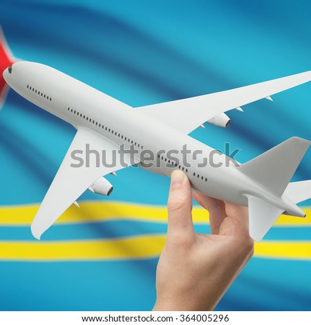 Airplane in hand with national flag on background series - Aruba - stock photo