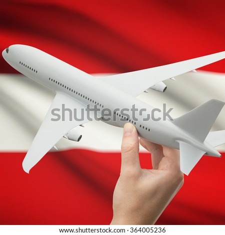 Airplane in hand with national flag on background series - Austria - stock photo