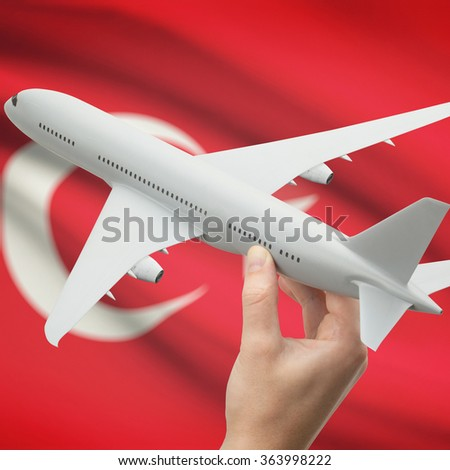 Airplane in hand with national flag on background series - Turkey - stock photo