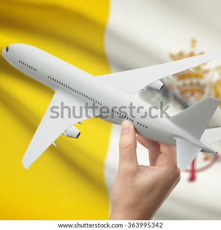 Airplane in hand with national flag on background series - Vatican City State - stock photo