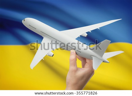 Airplane in hand with national flag on background - Ukraine - stock photo