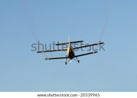 Airplane in low flight spraying, isolated over blue sky