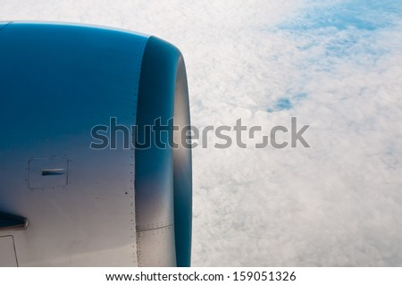 Airplane in the blue sky engine and wings white clouds